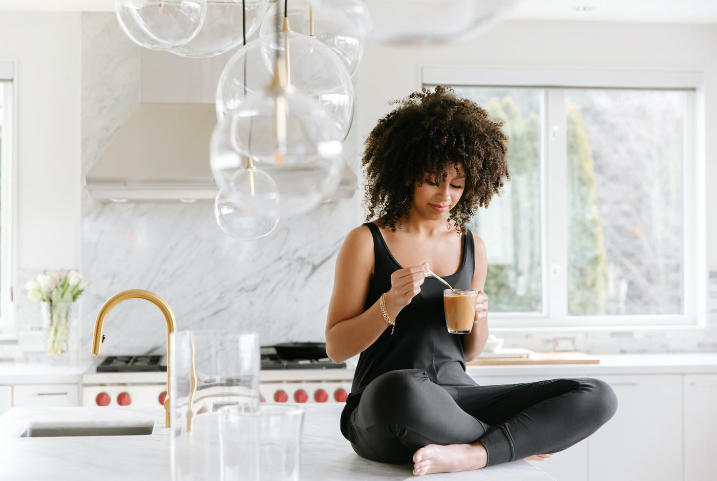 model wearing black smash + tess romper drinking coffee in the kitchen