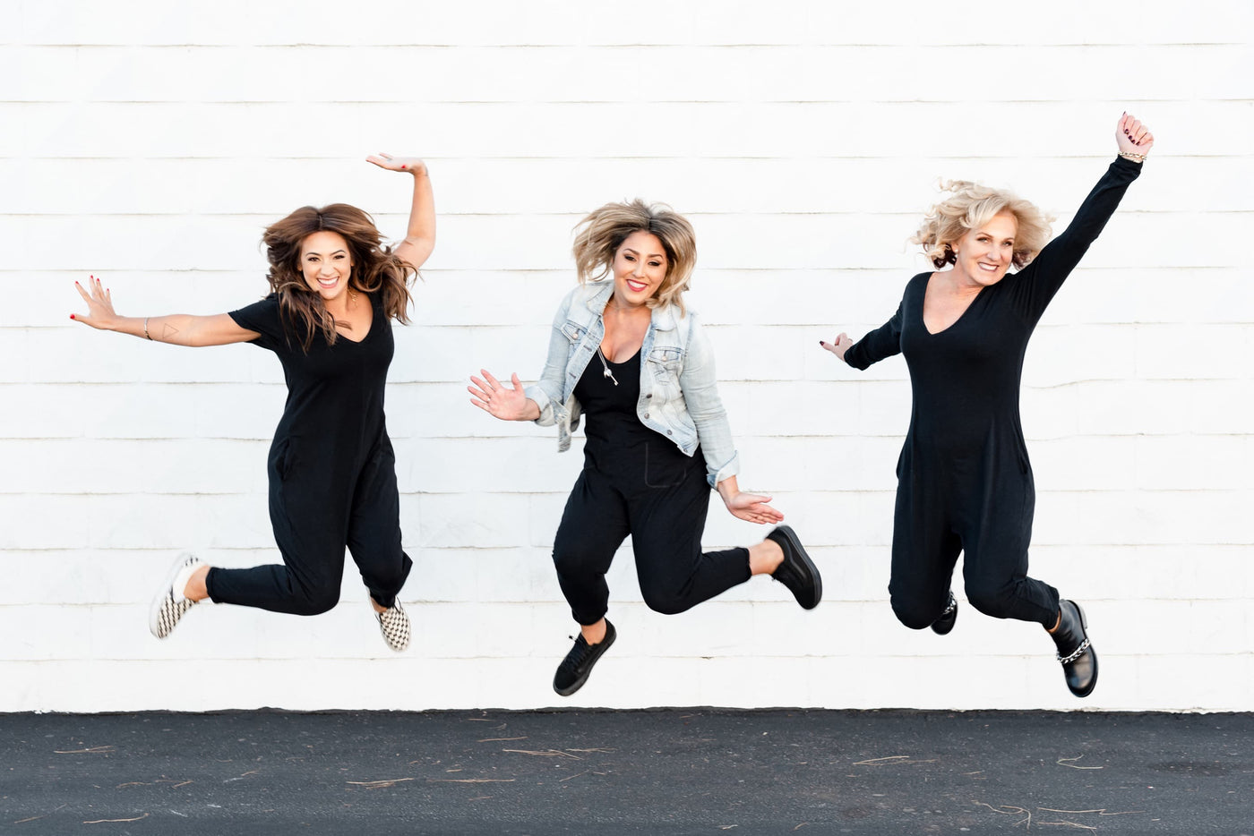 Founders of Smash + Tess jumping in front of a white wall