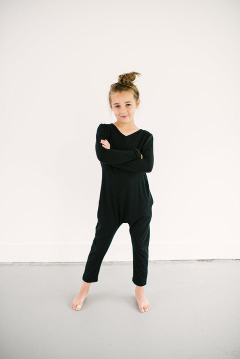The Mini Friday Romper, long sleeve black jumpsuit for girls | London is 8yrs wearing a 8/9
