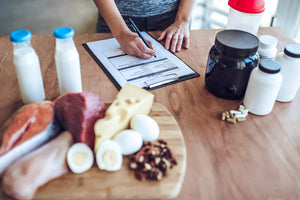 how much protein do you really need: woman writing with sports nutrition