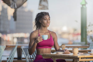 coffee before workout: woman wearing sports attire and holding a cup of coffee