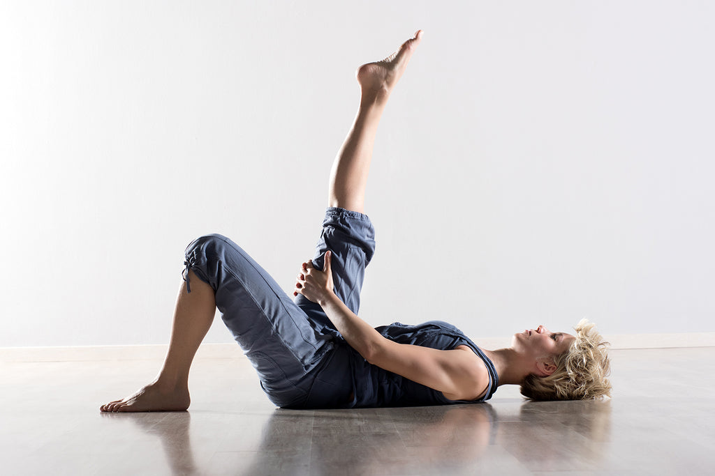 Woman lays on the ground and holds up extended leg