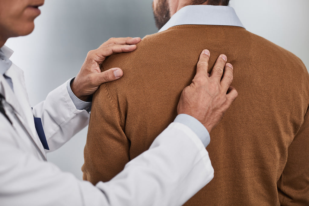 Thoracic spine mobility exercises: Doctor touching the spine of patient