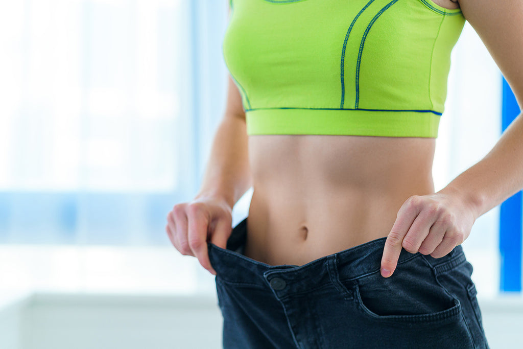 how long does it take to get into shape: Slim woman holding her large jeans