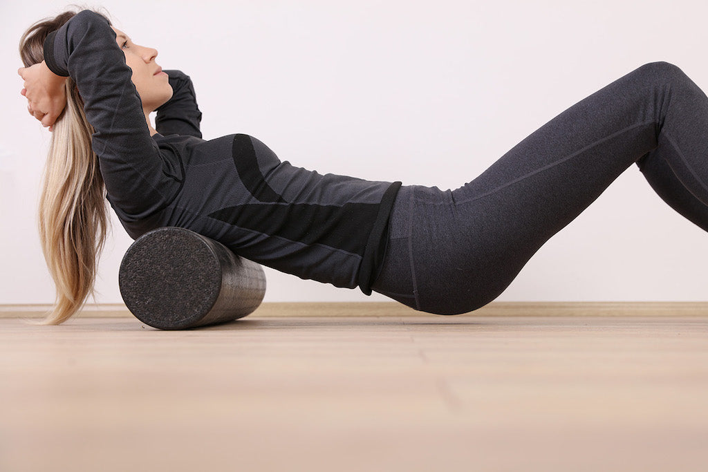 how long does your body need to rest between muscle training workouts?: girl using a foam roller