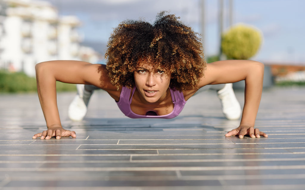 Woman doing a pushup as part of an upper body workout at home