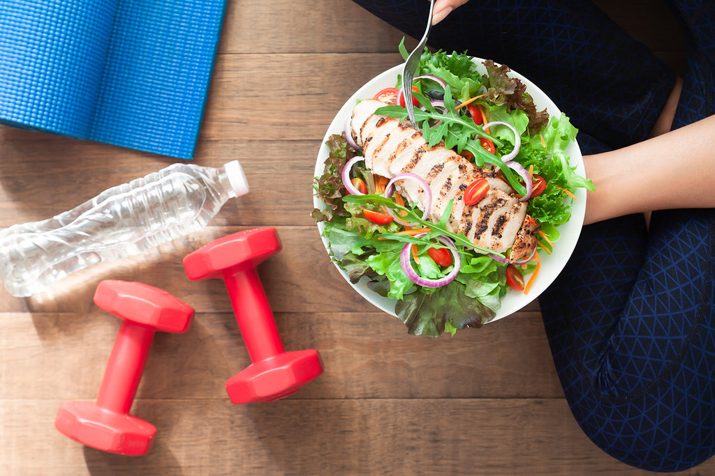 habits of health: water bottle, dumbbells and a woman holding a healthy food
