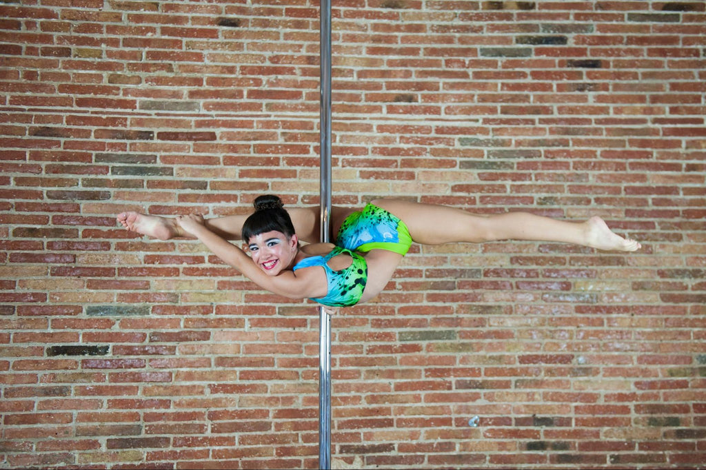 pole fitness: woman smiling while pole dancing