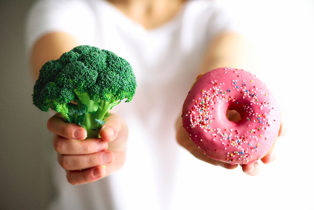 how to stop eating junk food: Woman holding a broccoli and donut