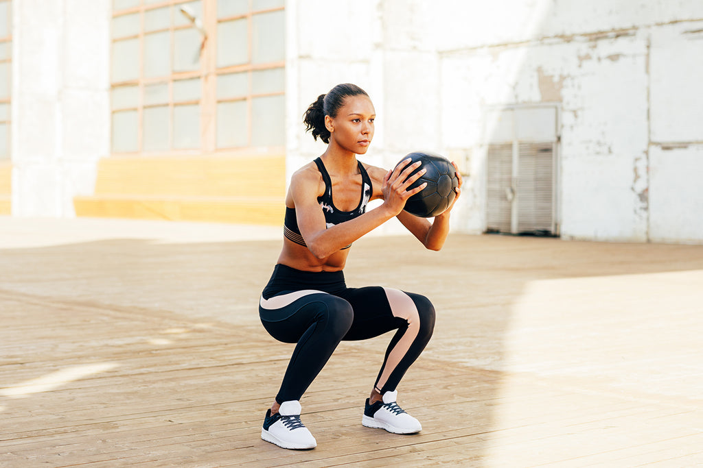 Female doing sissy squats exercise with medicine ball