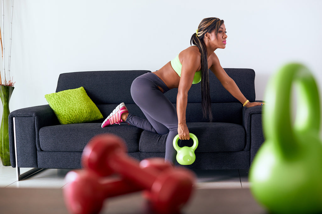 Hypertrophy vs Strength: Woman training using weights on sofa