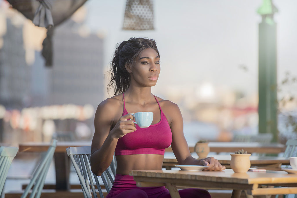 coffee before workout: woman in a sports outfit and holding a cup of coffee