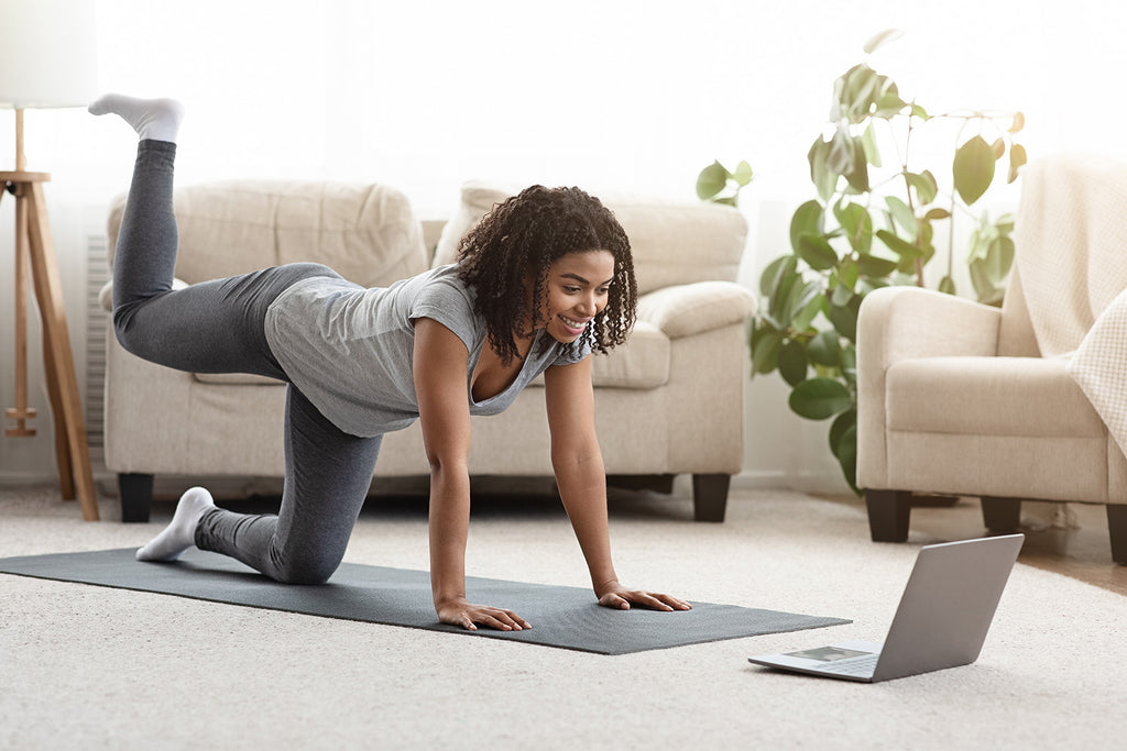 why is it often easier to start a fitness program than it is to maintain one?: Young woman exercising at home while watching a video tutorial on her laptop