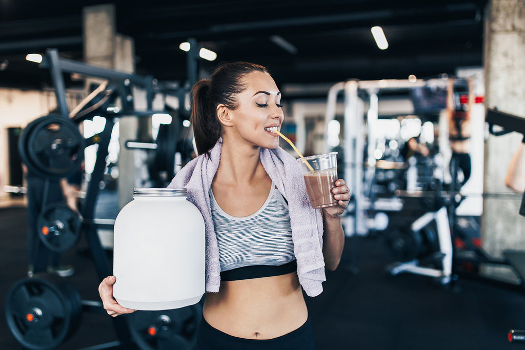 woman holding big white protein jar and drinks shake with drinking straw in other hand