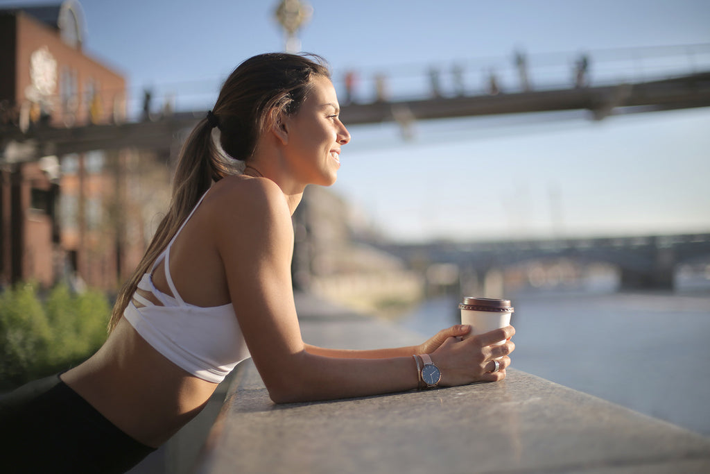 coffee before workout: woman in a sports outfit having coffee while looking at the river