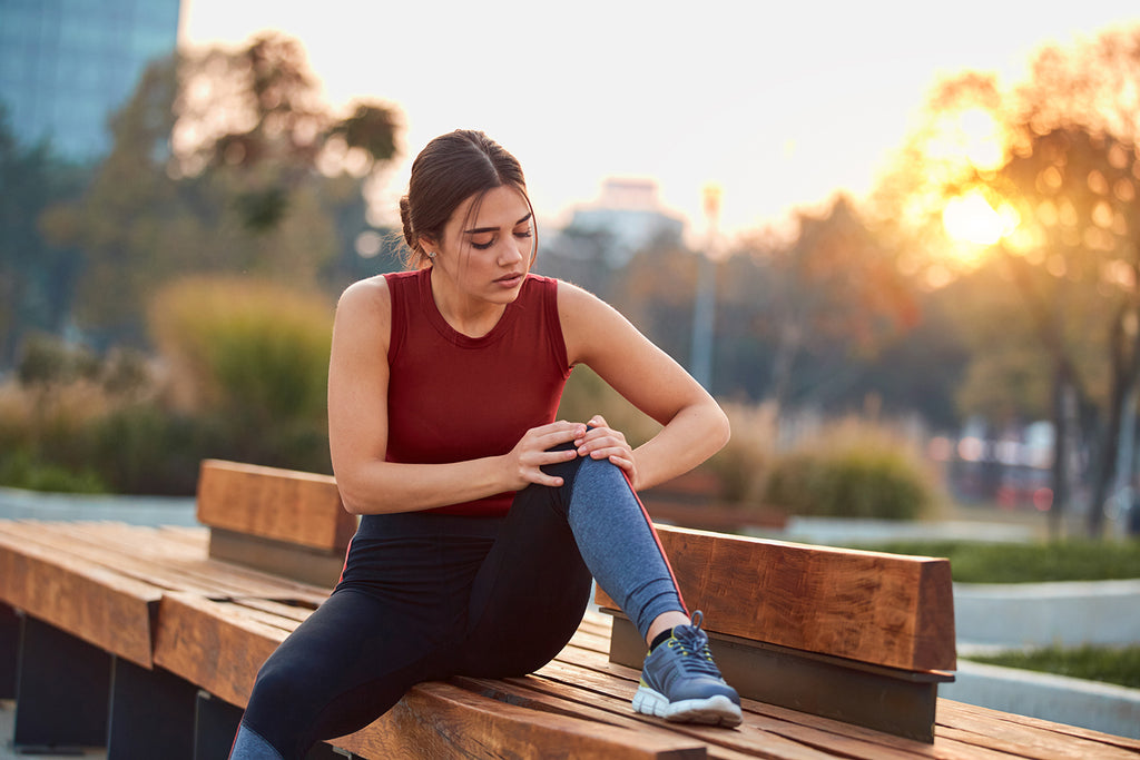 delayed onset muscle soreness: woman sitting on bench holding her knee