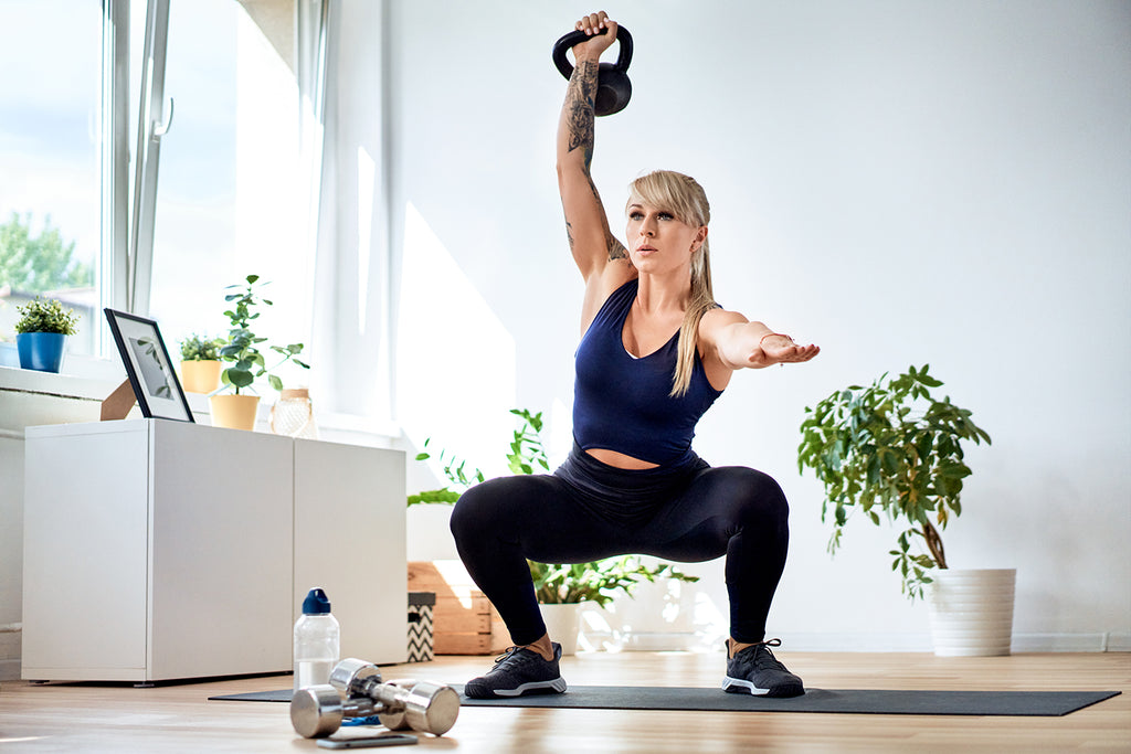 woman doing kettlebell exercises at home