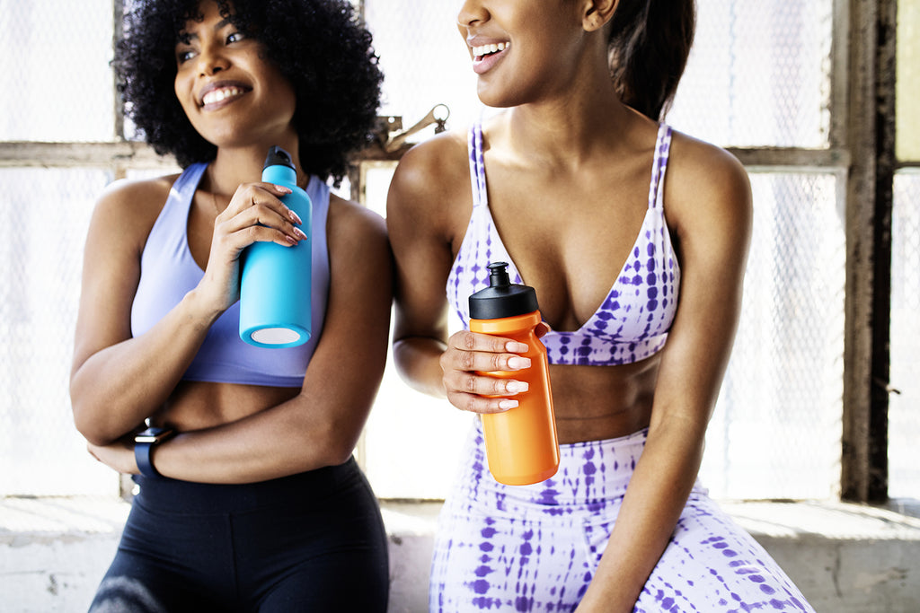 how much protein do you really need: two young women rehydrating at the gym
