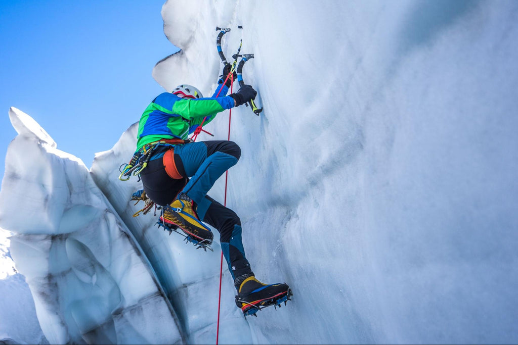 ice climbing: person reaching the top of the Alps