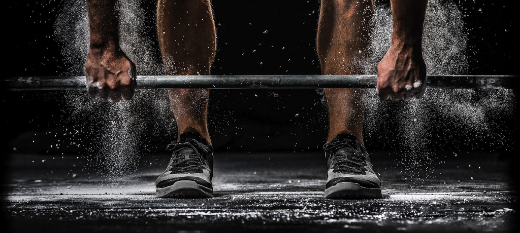 Types of deadlifts: Man lifting a barbell