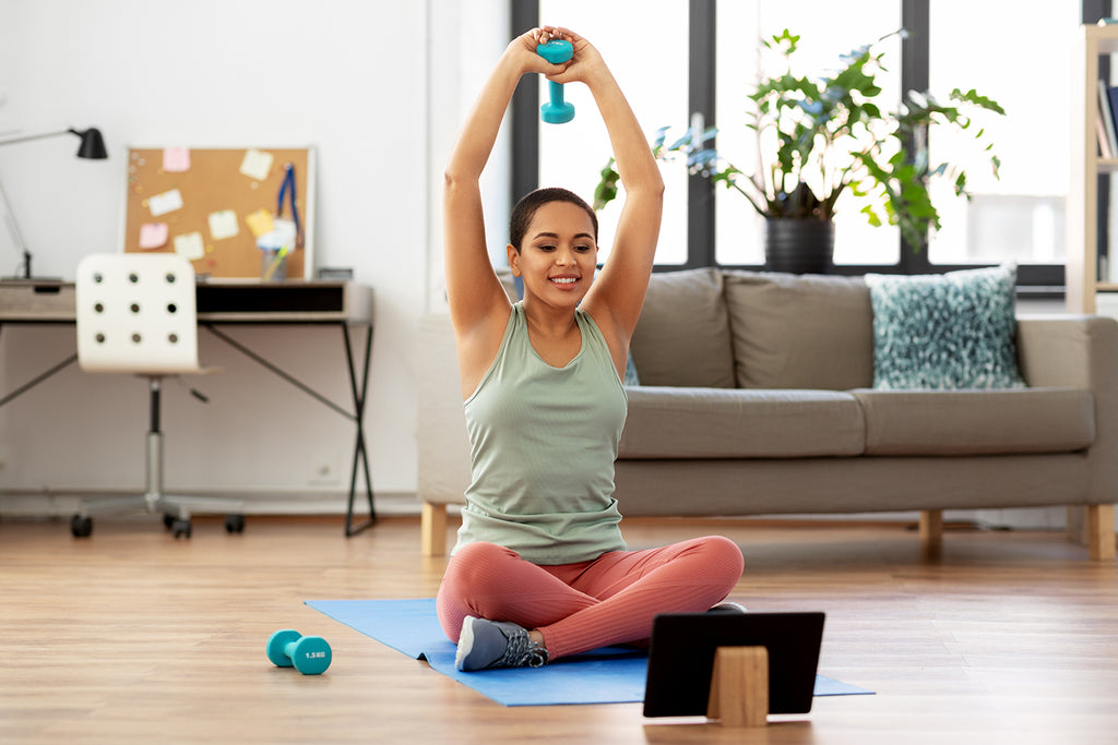 Woman sitting on the floor exercising using dumbbells