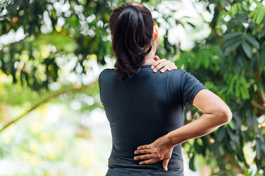 Woman holding her sore back muscles