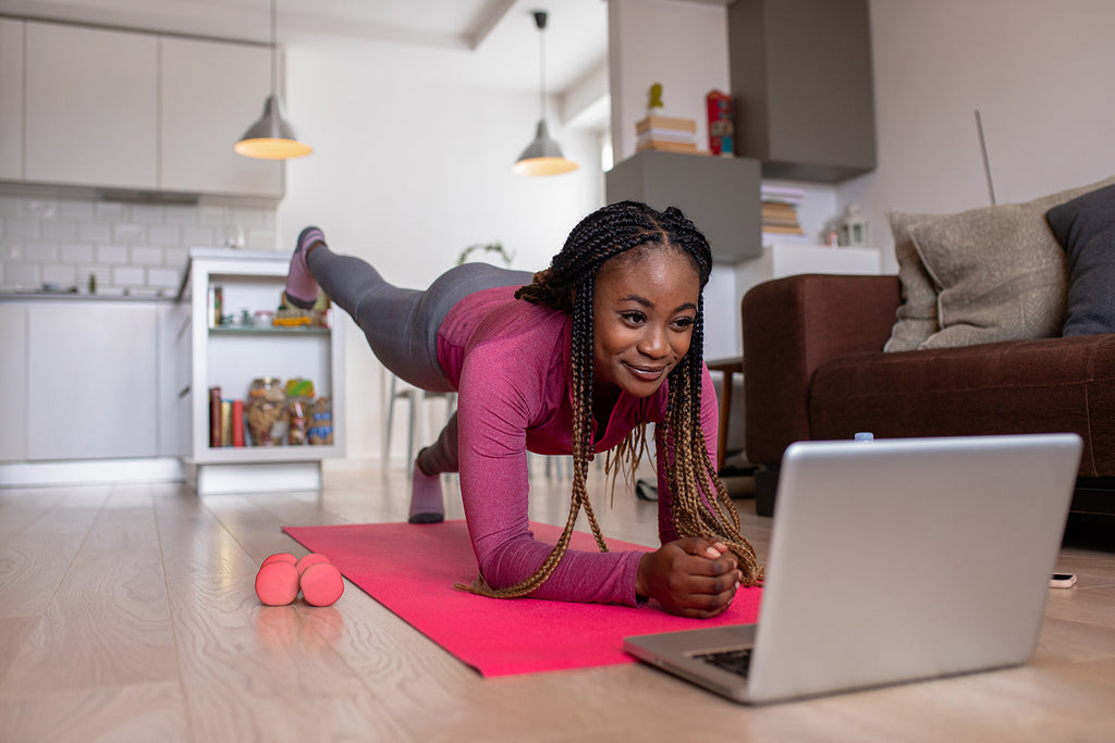 why is it often easier to start a fitness program than it is to maintain one?: Woman exercising at home while watching a video on her laptop