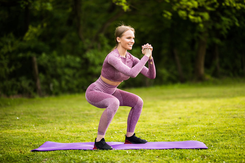 Woman doing air squats in the park