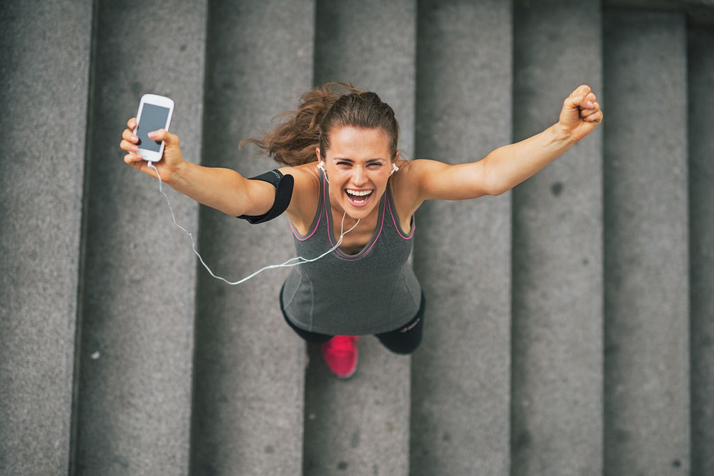 long term effects of exercise: woman in gym clothes smiling on a set of stairs