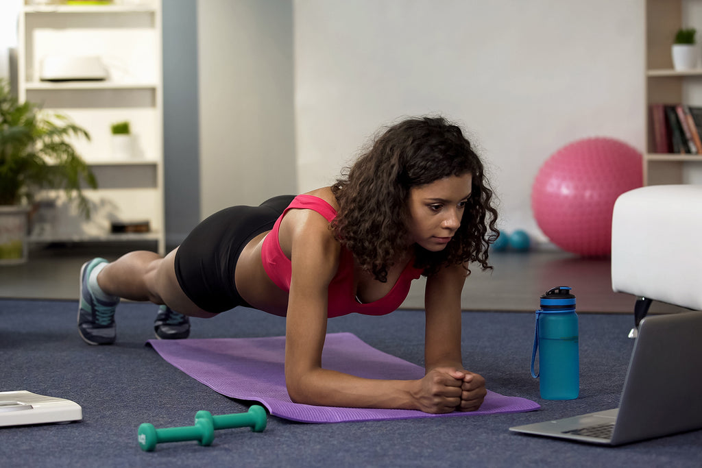how long does it take to get into shape: Woman doing online workout in front of her laptop