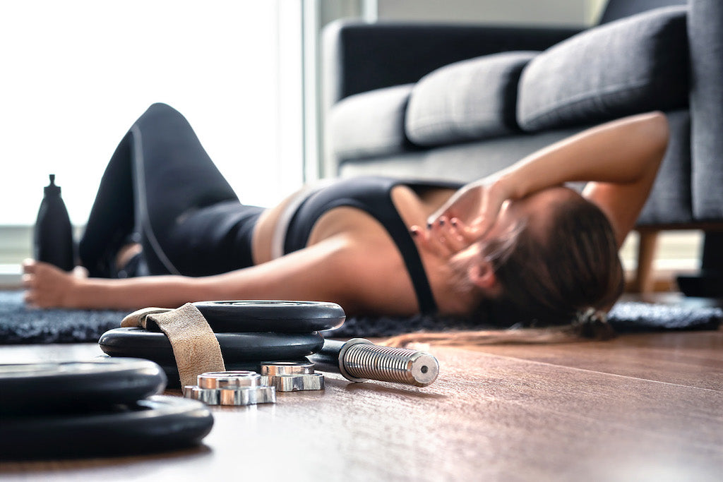 how long does your body need to rest between muscle training workouts?: girl laying down with weights on the floor