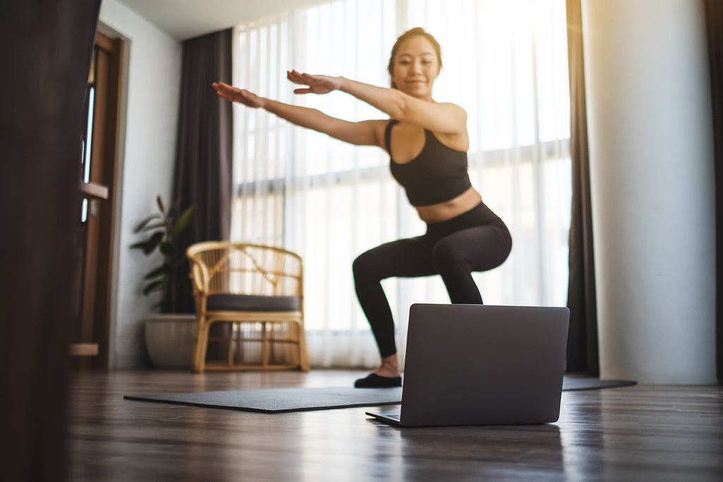 Woman doing squats while watching online workout tutorials on laptop