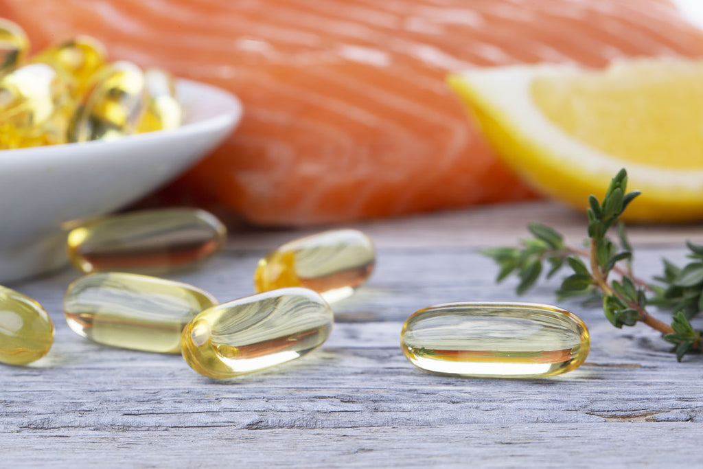 omega 3 6 9: tablets of omega-3 with a sliced lemon and salmon in the background