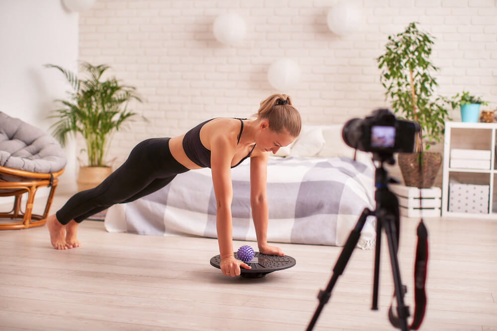 woman taking a video while using a balance board