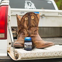 Leather boots in the back of a pickup truck, with a Straight Up Souther drink koozie
