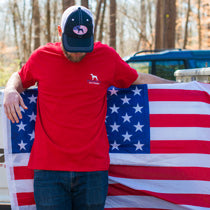 A man wearing a Straight Up Southern t-shirt holds an American flag