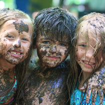 Three children smile for the camera while covered in mud