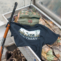 A Straight Up Southern t-shirt is draped over a box of hunting gear, including a rifle, boots, and camouflage