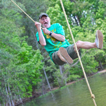 A man shouts with excitement while swinging on a rope over water