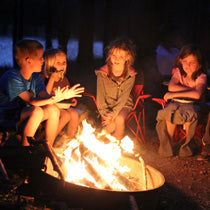 Four kids warm themselves by a campfire at night
