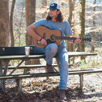 A man with long hair, a baseball cap, a guitar, and a Straight Up Southern t-shirt sits on a picnic table