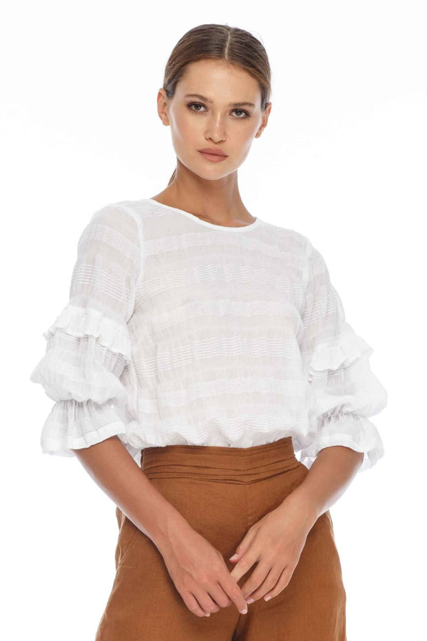BLAK WANDERER TOP - WHITE  The Blak Wanderer Top is a gorgeous semi-sheer top perfect for the warmer seasons. The Wanderer Top is soft to the touch and features a gentle crinkle embossed pattern throughout, a high gently curved neckline, with ruched elasticated cuffed half-sleeves sporting ruffles, finished with a deep v cutout at the back, and a tie detail.