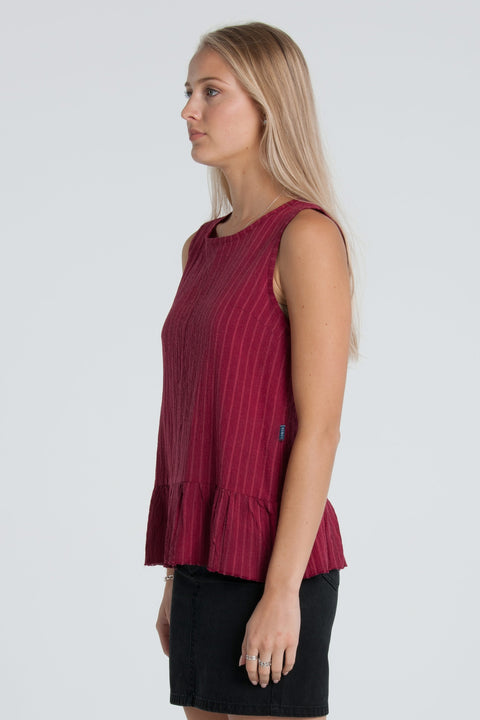 LOWER FRIDA TOP - CHERRY  The Lower Frida Top is an easy to wear top great for the warmer seasons. Simple, yet fun the Friday Top features a scooped neckline, with an oversized raw ruffled hemline, and back zip closure. Crafted from cotton, the Friday top is soft yet breathable. Wear the Lower Frida Top with jeans to skirts, layer or wear alone.