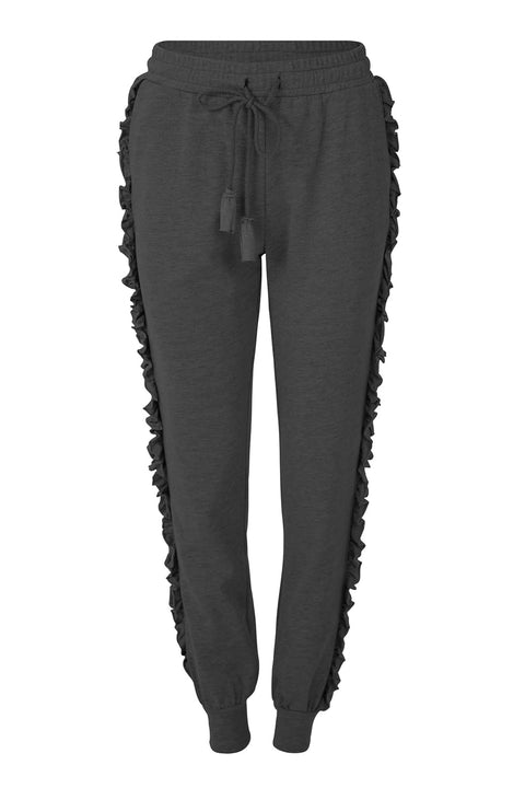 COOP YOU FRILL ME PANT - BLACK  The Coop You Frill Me Pants are now available in Black and are a fun feminine take on classic track pants. The You Frill Me Pants are relaxed fitting and feature drawstrings, with cotton tassels to fasten the elasticated waistband, two classic pockets, and ribbed leg cuffs, finished with a vertical raw-edge feminine ruffle detail on each side. Stylish, practical and comfortable, mix and match with your favourite COOP sweatshirts for an on-trend casual look.