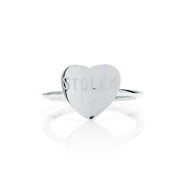 "Stolen Girlfriends Club Stolen Heart Ring Stolen Girlfriends Club Stolen Heart Ring is basic heart ring featuring the iconic ""Stolen"" engraved on the front, crafted from high polish sterling silver."
