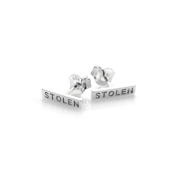 "STOLEN GIRLFRIENDS CLUB TINY STOLEN BAR EARRINGS - SILVER  The Stolen Girlfriends Club Stolen Bar Earrings are the perfect gift for a Stolen fan. They are a stud earring with a 1.3cm sterling silver bar featuring the words ""STOLEN"" engraved on each.  -Engraved ""STOLEN"" -Sterling Silver  -Sold as a pair"