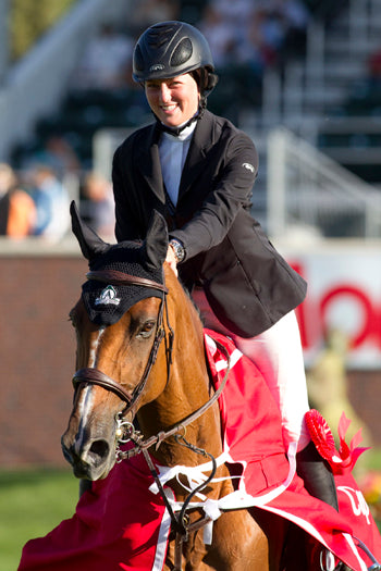 Caitlin Ziegler with Valencia in their victory lap at Spruce Meadows