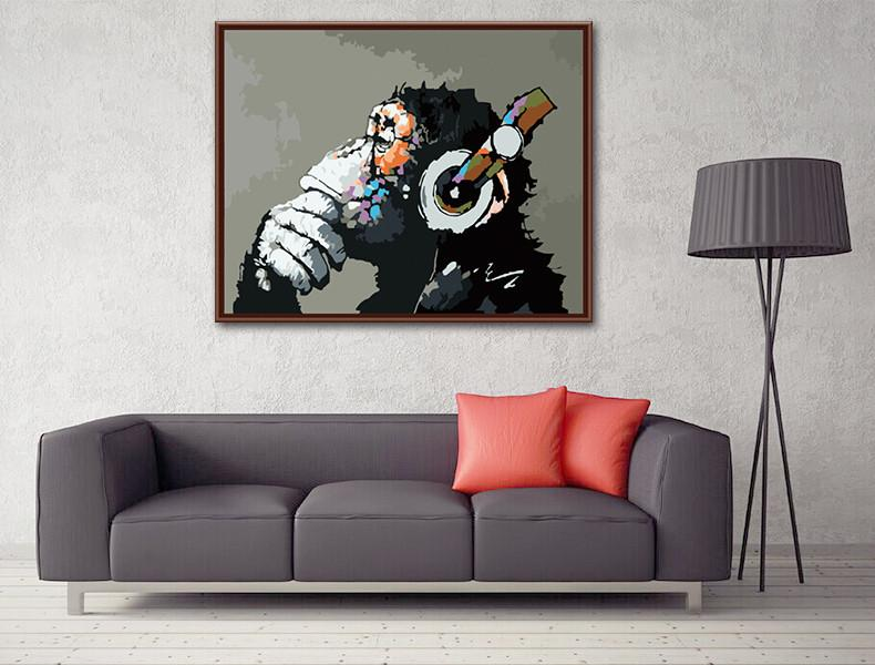 banksy picture of monkey with headphones hanging picture above couch