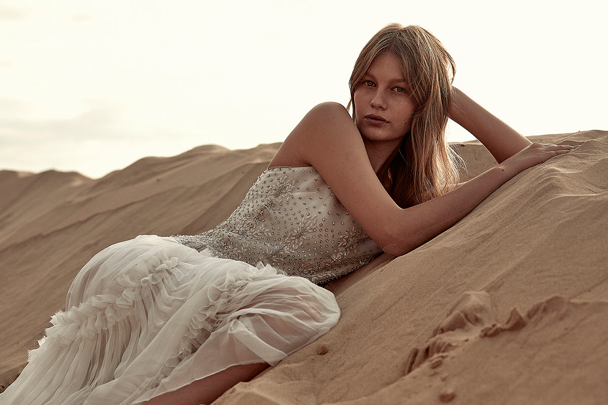 Lying on the dessert with a white dress