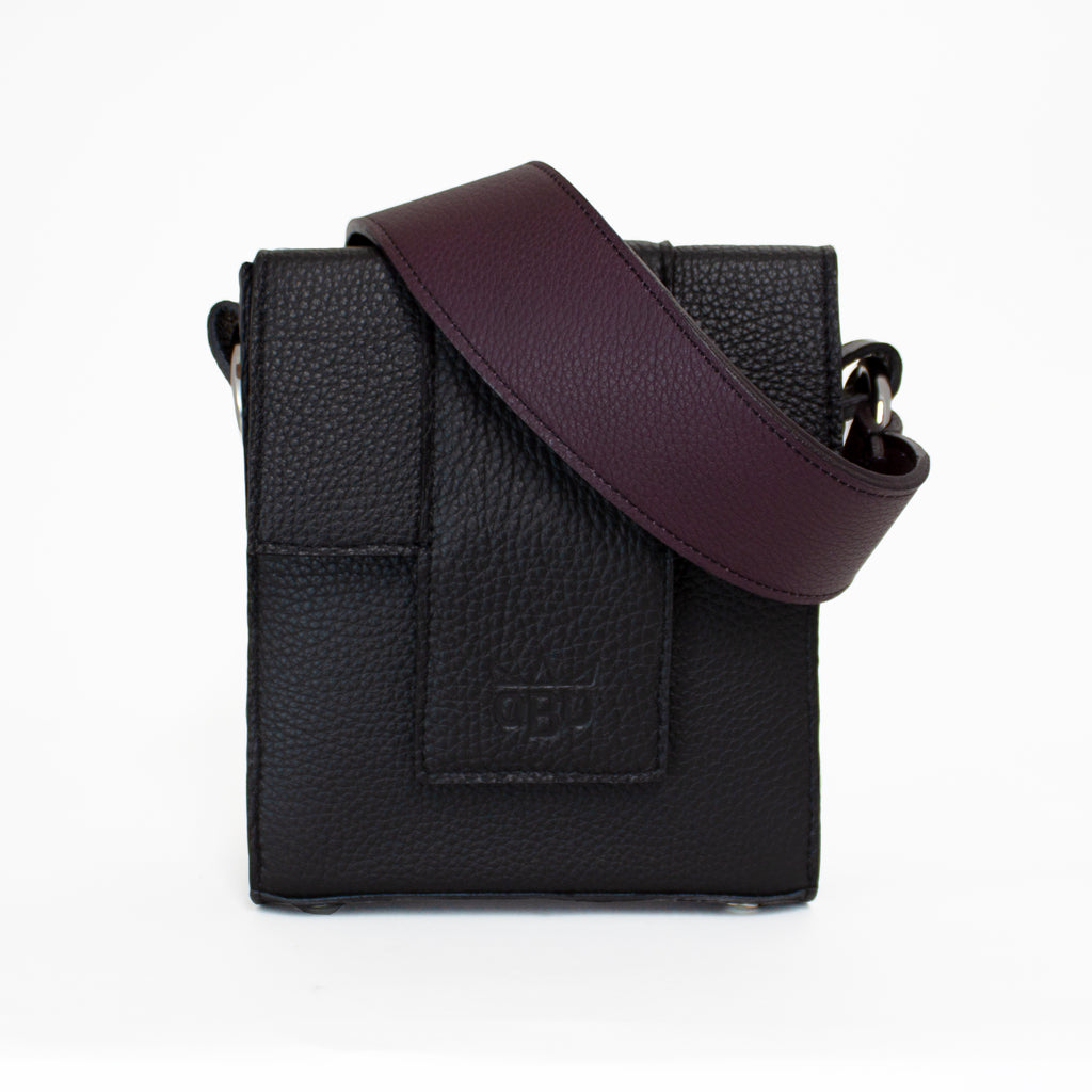 Aubergine purple strap for a tonal look with this edgy black leather bag. Irish designed accessories. Scottish made and from zero impact sustainable Italian leather.